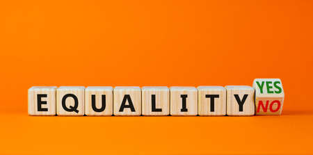 Equality symbol. Turned a wooden cube and changed words 'equality no' to 'equality yes'. Beautiful orange background. Business and equality concept, copy space. 스톡 콘텐츠