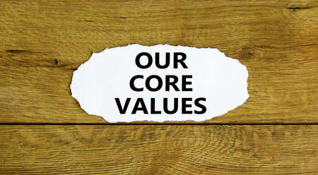 Our core values symbol. Words 'Our core values' on white paper. Beautiful wooden background. Business and our core values concept. Copy space.
