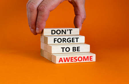 Do not forget awesome symbol. Concept words 'Do not forget awesome' on wooden blocks on a beautiful orange background. Businessman hand. Business, motivational, be awesome concept. Stock Photo