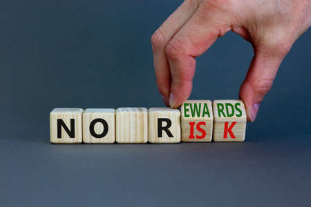 No risk and rewards symbol. Businessman turns wooden cubes and changes words 'no risk' to 'no rewards'. Beautiful grey background. No risk and rewards, business concept. Copy space.
