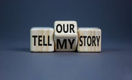 Tell my or our story. Turned wooden cubes and changed words tell my story to tell our story. Beautiful grey background, copy space. Business, storytelling and my or our story concept.