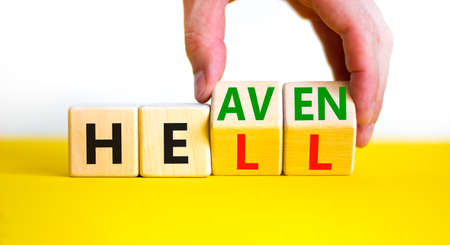 Hell or heaven symbol. Businessman turns wooden cubes and changes the word 'hell' to 'heaven'. Beautiful white background, copy space. Busines, religion and hell or heaven concept.