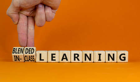 Blended or in-class learning symbol. Businessman turns cubes, changes words blended learning to in-class learning. Orange background. Education and blended or in-class learning concept. Copy space.