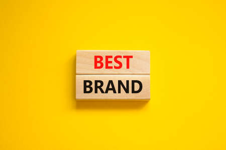 Best brand symbol. Concept words Best brand on wooden blocks on a beautiful yellow background. Business and best brand concept. Copy space. Stock Photo