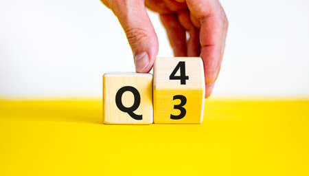 From 3rd to 4th quarter symbol. Businessman turns a wooden cube and changes words 'Q3' to 'Q4'. Beautiful yellow table, white background. Business, happy 4th quarter Q4 concept, copy space.