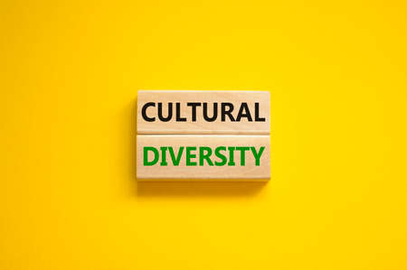 Time to cultural diversity symbol. Wooden blocks with words 'Cultural diversity'. Beautiful yellow background. Business and cultural diversity concept. Copy space. Stock Photo