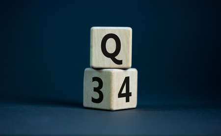 From 3rd to 4th quarter symbol. Turned wooden cubes and changed words 'Q3' to 'Q4'. Beautiful grey table, grey background. Business, happy 4th quarter Q4 concept, copy space. Stock Photo