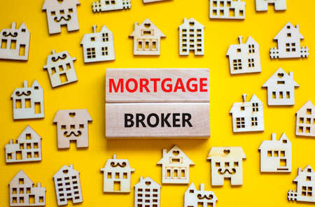 Mortgage broker symbol. Concept words 'Mortgage broker' on wooden blocks near miniature wooden houses. Beautiful yellow background. Business, mortgage broker concept.
