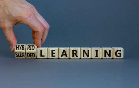 Blended or hybrid learning symbol. Businessman turns cubes, changes words blended learning to hybrid learning. Grey background. Business, education and blended or hybrid learning concept. Copy space.