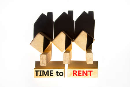 Time to rent house symbol. Concept words 'Time to rent' on wooden blocks near miniature houses from shadows. Beautiful white background, copy space. Business and time to rent house concept. Stock Photo