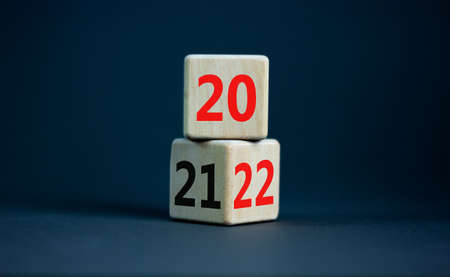 2022 happy new year symbol. Turned cubes, symbolize the change from 2021 to the new year 2022. Beautiful grey table, grey background. Copy space. Business and 2022 happy new year concept.