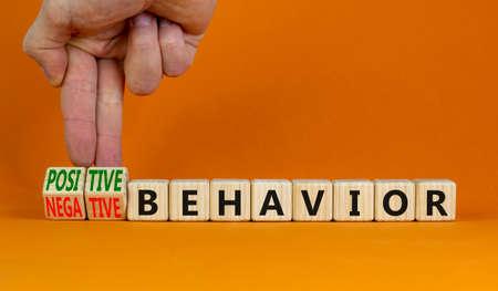 Positive or negative behavior symbol. Businessman turns cubes, changes words negative behavior to positive behavior. Orange background, copy space. Psychology, positive or negative behavior concept.