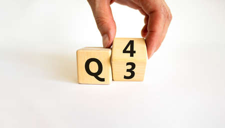 From 3rd to 4th quarter symbol. Businessman turns a wooden cube and changes words 'Q3' to 'Q4'. Beautiful white table, white background. Business, happy 4th quarter Q4 concept, copy space.