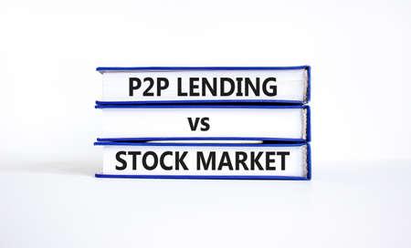 P2P, peer to peer lending vs stock market symbol. Concept words 'P2P lending vs stock market' on books. Beautiful white background, copy space. Business and P2P lending vs stock market concept.