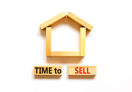 Time to sell house symbol. Concept words 'Time to sell' on wooden blocks near miniature house. Beautiful white background, copy space. Business and time to sell house concept.