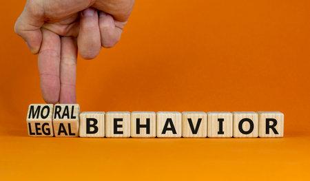 Moral or legal behavior symbol. Businessman turns cubes, changes words legal behavior to moral behavior. Beautiful orange background, copy space. Psychology, moral or legal behavior concept.
