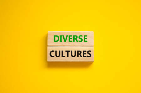 Time to diverse cultures symbol. Wooden blocks with words 'Diverse cultures'. Beautiful yellow background. Business and diverse cultures concept. Copy space.