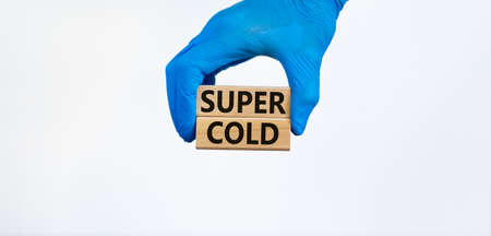 Super cold symbol. Words Super cold on wooden blocks. Doctor hand in blue glove. Beautiful white background. Stock Photo
