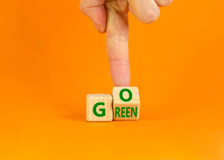 Ecology and go green symbol. Businessman turns a wooden cube with concept words 'Go green' on a beautiful orange table, orange background. Copy space. Business and go green concept.