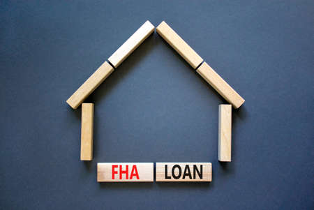 FHA federal housing administration loan symbol. Concept words 'FHA federal housing administration loan' on wooden blocks on a beautiful grey background. Business and FHA loan concept. Copy space.