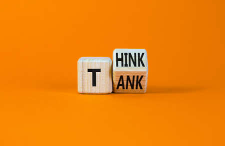 Think tank symbol. Turned a wooden cube and changed the word 'tank' to 'think' or vice versa. Beautiful orange table, orange background, copy space. Business, think tank concept. Stock Photo