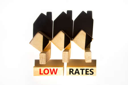 Low house rates symbol. Concept words 'Low rates' on wooden blocks near miniature houses from shadows. Beautiful white background, copy space. Business and low house rates concept. Stock Photo
