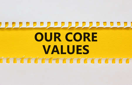 Our core values symbol. White and yellow paper with words 'Our core values'. Beautiful yellow background. Business and our core values concept. Copy space. Stock Photo