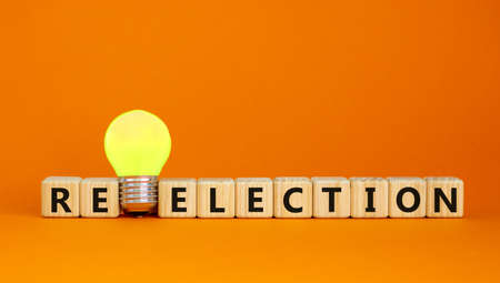 Election or reelection symbol. Cubes with words 'Election reelection'. Yellow light bulb. Beautiful orange background. Business, politic, election or reelection concept. Copy space.