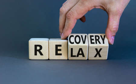 Relax and recovery symbol. Businessman turns cubes and changes the word 'relax' to 'recovery'. Beautiful grey table, grey background. Business, relax and recovery concept. Copy space. Stock Photo