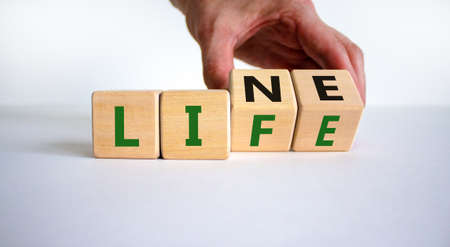 Lifeline, line of life symbol. Businessman hand turns cubes and changes the word 'life' to 'line'. Beautiful white background. Business lifeline, line of life concept. Copy space.