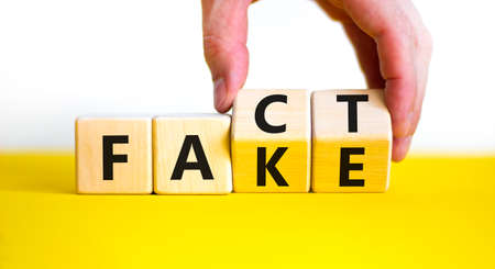 Fact or fake symbol. Businessman turn wooden cubes and changes the word 'fake' to 'fact' concept on beautiful white background, copy space. Business and fake or fact concept.