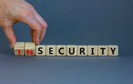 Security or insecurity symbol. Businessman turns wooden cubes, changes words insecurity to security. Beautiful grey background. Business, security or insecurity concept. Copy space. Stock Photo