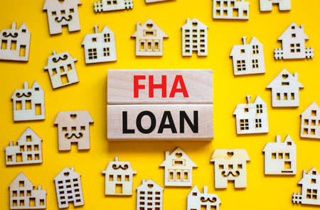 FHA federal housing administration loan symbol. Concept words 'FHA federal housing administration loan' on wooden blocks on a beautiful yellow background. Business and FHA loan concept. Copy space.