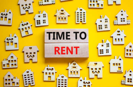 Time to rent house symbol. Concept words 'Time to rent' on wooden blocks near miniature houses. Beautiful yellow background, copy space. Business and time to rent house concept.