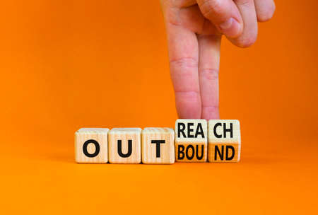 Outreach or outbound symbol. Businessman turns wooden cubes and changes the word 'outbound' to 'outreach'. Beautiful orange table orange background. Business, outreach or outbound concept. Copy space. Stock Photo