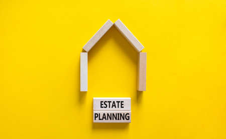 Estate planning symbol. Concept words 'Estate planning' on wooden blocks near miniature house. Beautiful yellow background, copy space. Business and estate planning concept.
