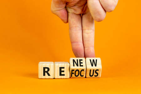 Refocus and renew symbol. Businessman turns cubes and changes the word 'refocus' to 'renew'. Beautiful orange table, orange background. Business refocus and renew concept. Copy space. Stock Photo
