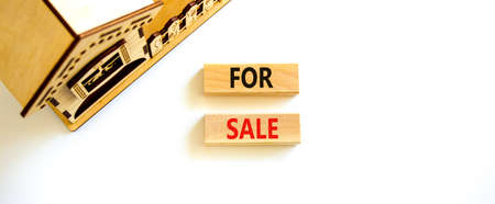 House for sale symbol. Concept words 'For sale' on wooden blocks near miniature house. Beautiful white background, copy space. Business and house for sale concept. Stock Photo