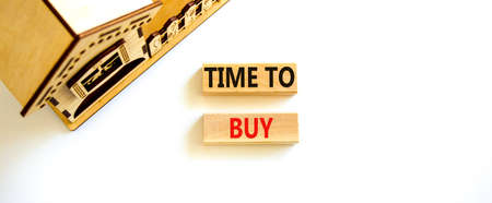 Time to buy house symbol. Concept words 'Time to buy' on wooden blocks near miniature house. Beautiful white background, copy space. Business and time to buy house concept.