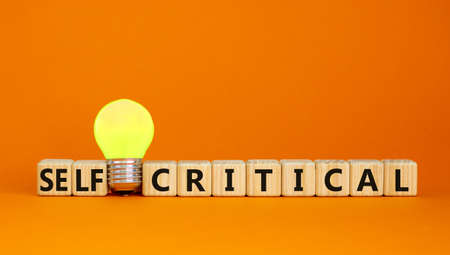 Critical or self-critical symbol. Cubes with words 'Self-critical or critical'. Yellow light bulb. Beautiful orange background. Psychology, critical or self-critical and business concept. Copy space.