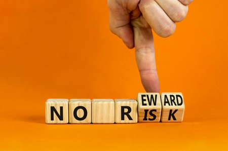 No risk and reward symbol. Businessman turns wooden cubes and changes words 'no risk' to 'no reward'. Beautiful orange background. No risk and reward, business concept. Copy space.
