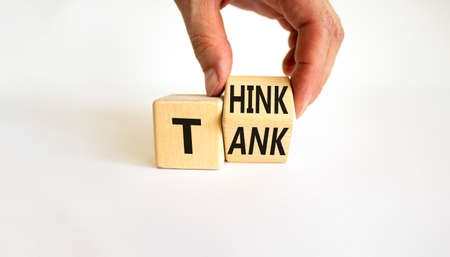 Think tank symbol. Businessman turns a wooden cube and changes the word 'tank' to 'think' or vice versa. Beautiful white table, white background, copy space. Business, think tank concept. Stock Photo
