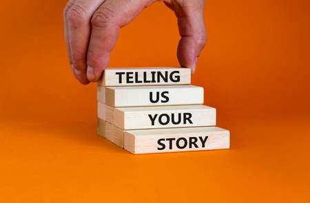 Telling us your story symbol. Wooden bloks with words 'Telling us your story'. Businessman hand. Beautiful orange background, copy space. Business, storytelling and telling us your story concept.