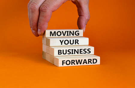 Moving your business forward symbol. Concept words 'Moving your business forward' on wooden blocks on a beautiful orange background. Businessman hand. Business, motivational, success concept.