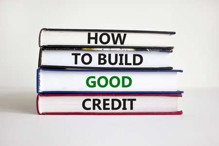 Symbol of building success foundation and good credit symbol. Books with words how to build good credit. Beautiful white background. Businessman hand. Business and build good credit concept. Stock Photo