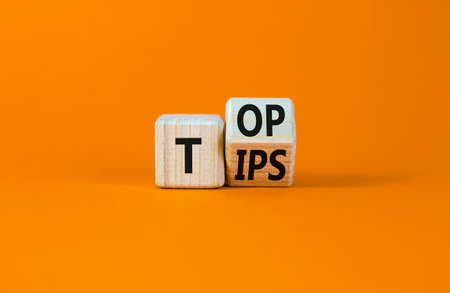 Top tips symbol. Turned a wooden cube with words 'Top tips'. Beautiful orange table, orange background. Top tips and business concept. Copy space.