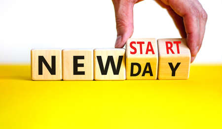 New day and start symbol. Businessman turns wooden cubes and changes words 'new day' to 'new start'. Beautiful yellow table, white background. Copy space. Business, new day and start concept.