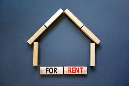 House for rent symbol. Concept words 'For rent' on wooden blocks near miniature house. Beautiful grey background, copy space. Business and house for rent concept.