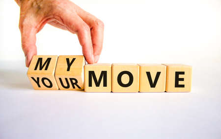 My or your move symbol. Businessman turns wooden cubes and changes words 'your move' to 'my move'. Beautiful white table, white background. My or your move and business concept. Copy space.