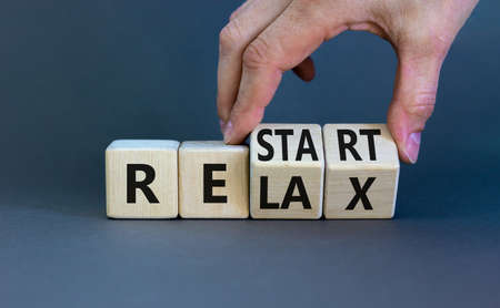 Relax and restart symbol. Businessman turns cubes and changes the word 'relax' to 'restart'. Beautiful grey table, grey background. Business, relax and restart concept. Copy space.